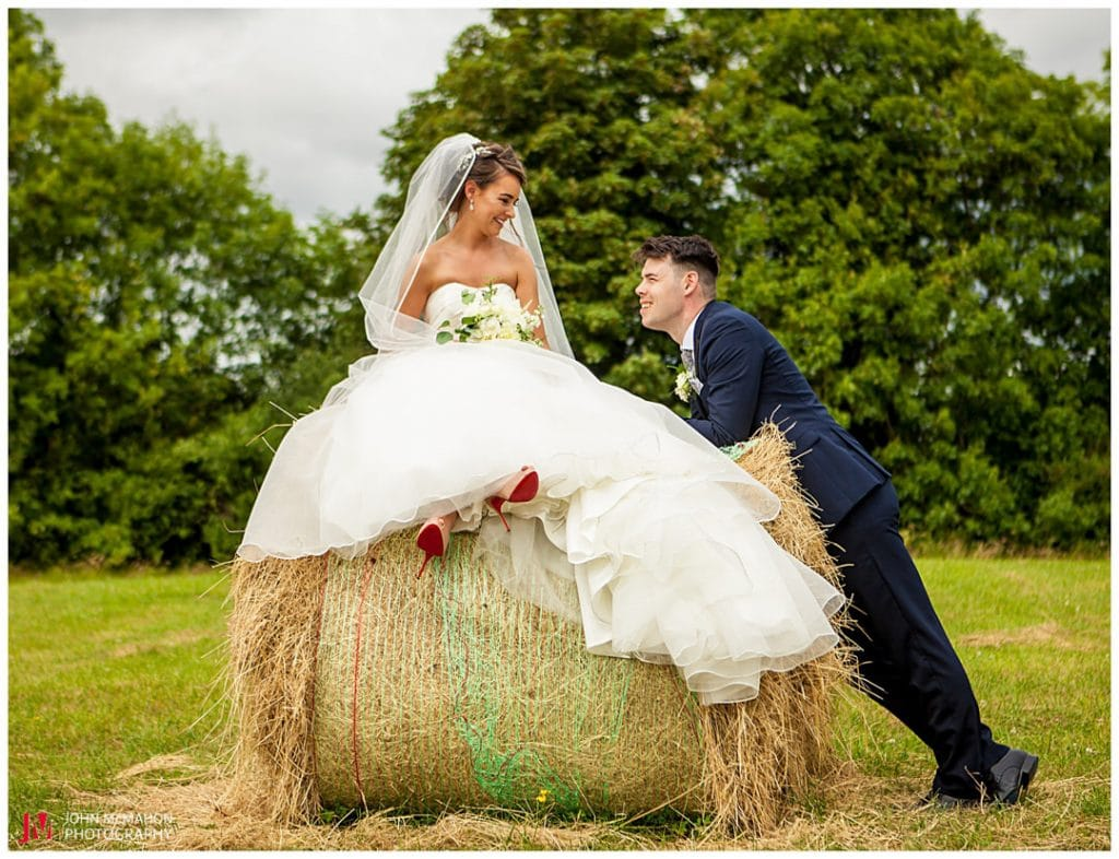 Bride sitting on a bale of hay