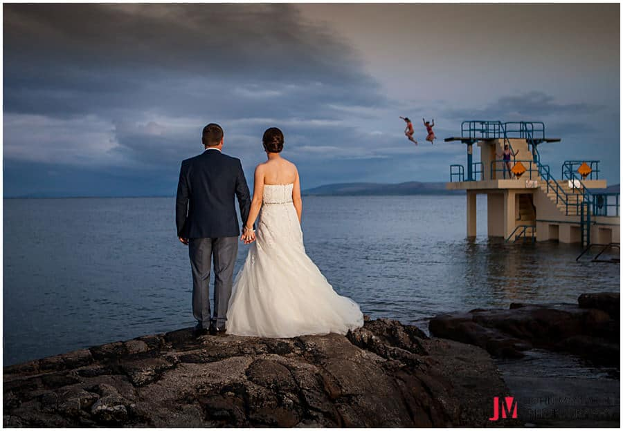 Bride and groom look at late night swimmers