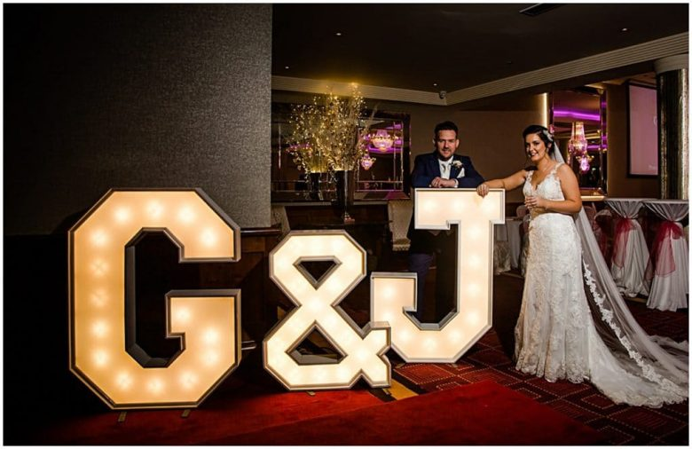 Bride and groom with large lettering on wedding day in Salthill Hotel